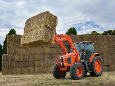 M Series Kubota Tractor with loader lifting bale